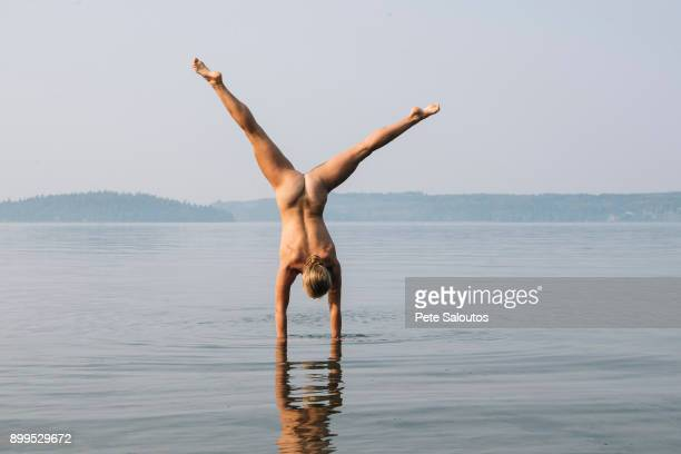 Rear view of nude woman doing handstand in water