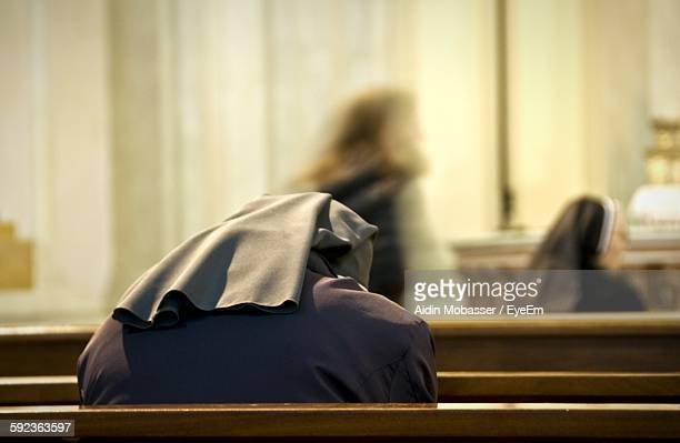 rear view of nun praying at church - bonne soeur photos et images de collection