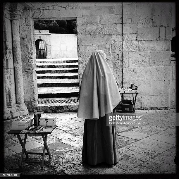 rear view of nun standing against wall - 聖職服 ストックフォトと画像