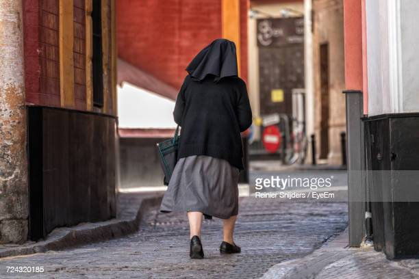 rear view of nun walking on city street - nun stock pictures, royalty-free photos & images