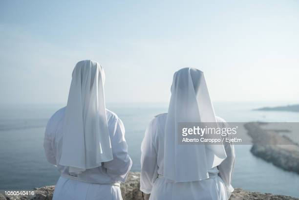 rear view of nuns standing on cliff by sea against clear sky - bonne soeur photos et images de collection