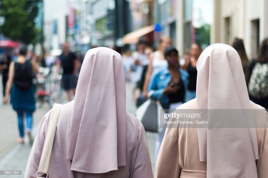 Rear View Of Nuns Walking On Street In City : Stock Photo