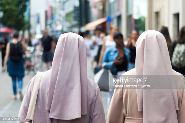 rear view of nuns walking on street in city - nun stock photos and pictures