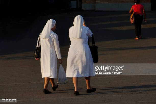 rear view of nuns walking on street - bonne soeur photos et images de collection