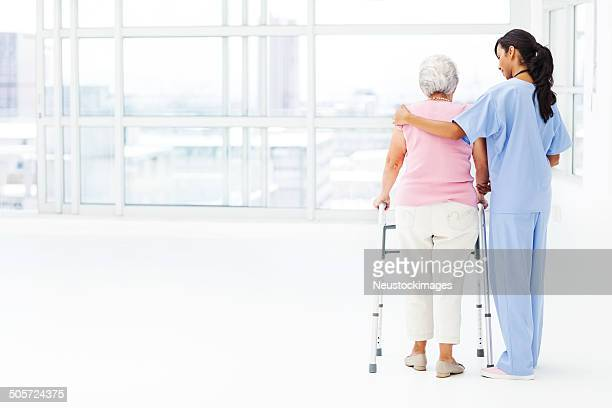 Rear View Of Nurse Assisting Senior Patient With Walker