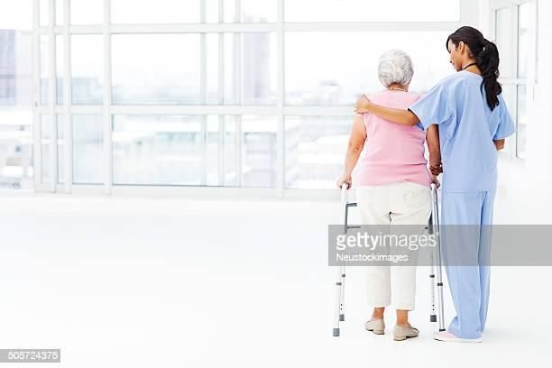 Vista posterior de enfermera ayudar a un paciente Senior con Walker