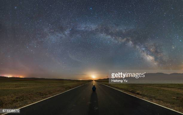 Rear view of one man sitting in middle of highway with milky way and rising moon