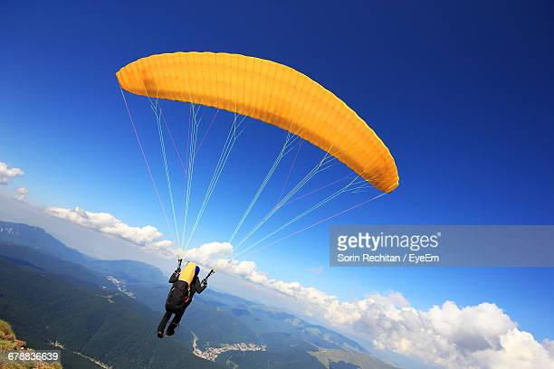 Rear View Of One Person Paragliding Over Mountains