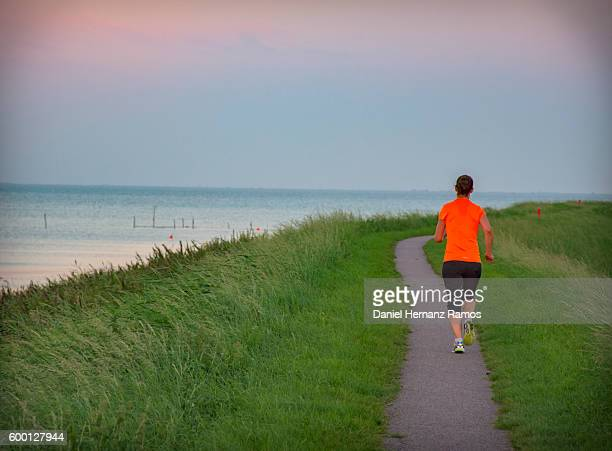 Rear view of one woman running in a path in countryside, surrounding by grass and the sea in the left