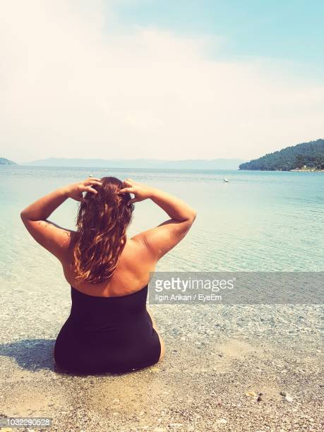 rear view of overweight woman looking at sea against sky - dicke frauen am strand stock-fotos und bilder