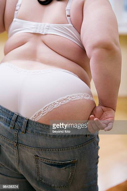 rear view of overweight woman trying to put on jeans trousers