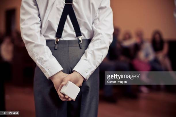 rear view of pageboy holding wedding ring box in ceremony - pageboy stock pictures, royalty-free photos & images