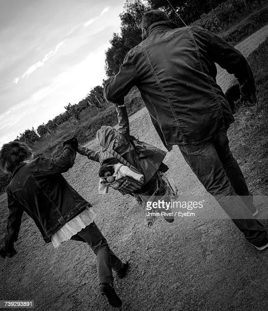 Rear View Of Parents Lifting Girl While Walking On Field Against Sky