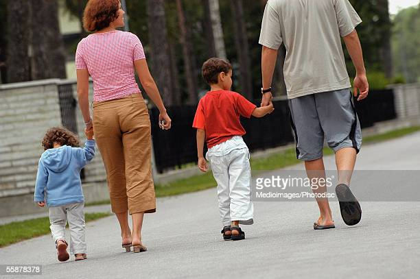 rear view of parents walking with their two children - pedal pushers stock pictures, royalty-free photos & images