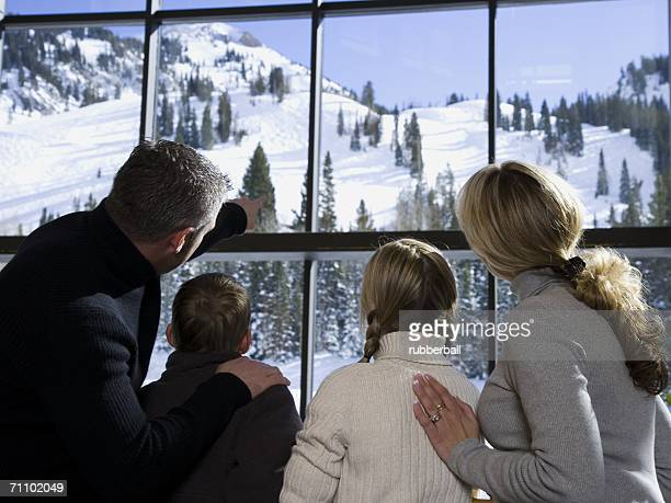 Rear view of parents with their son and daughter looking through a window