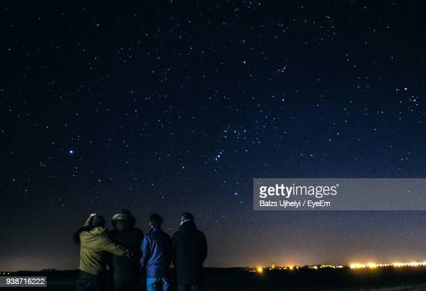 rear view of people against star field at night - astronomy stock pictures, royalty-free photos & images