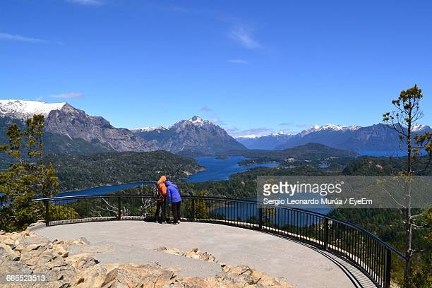 rear view of people at observation point by mountains against sky - bariloche stock pictures, royalty-free photos & images