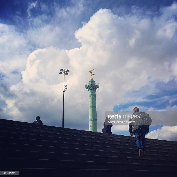 rear view of people by colonne de juillet at place de la bastille in city - bastille stock photos and pictures