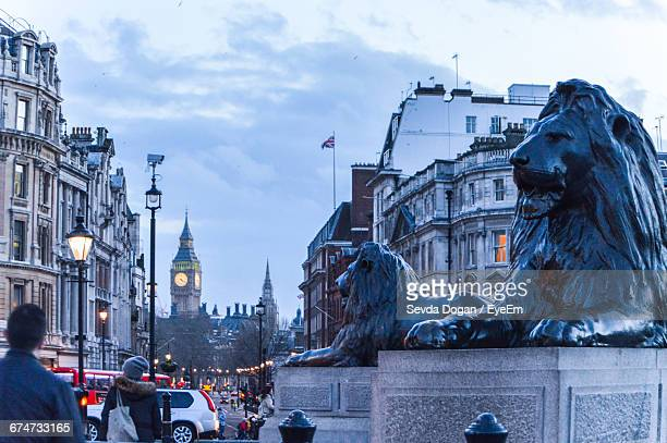 rear view of people by lion statues at trafalgar square against big ben - trafalgar square stock pictures, royalty-free photos & images