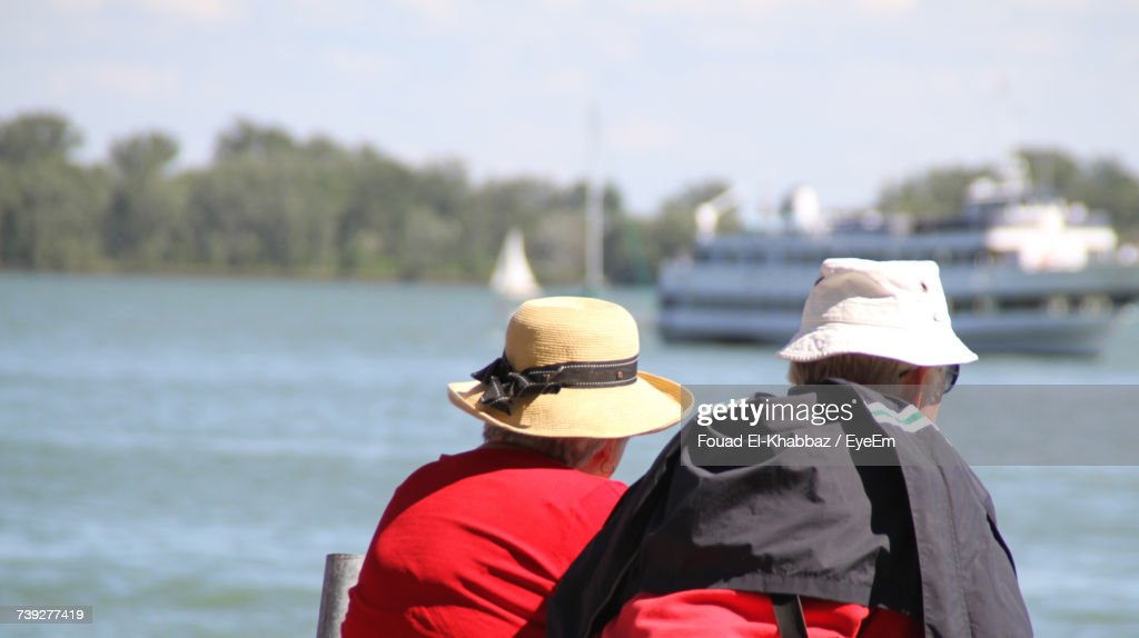 Rear View Of People By River Against Sky : Stock Photo