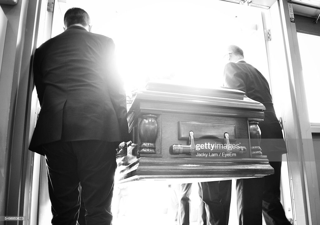 Rear View Of People Carrying Coffin : Stock Photo