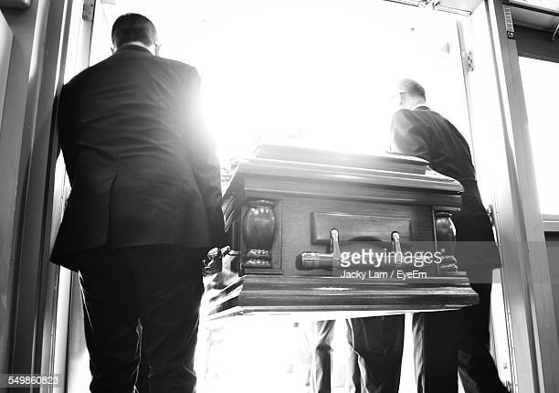 rear view of people carrying coffin - funeral stock pictures, royalty-free photos & images