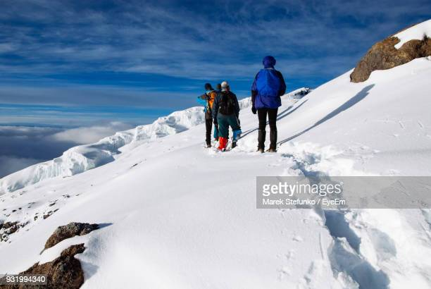 rear view of people climbing snow covered mountain - marek stefunko imagens e fotografias de stock
