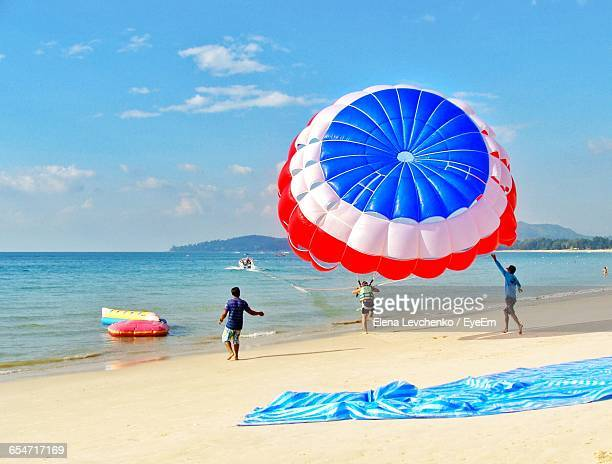 Rear View Of People Enjoying Paragliding At Beach Against Sky