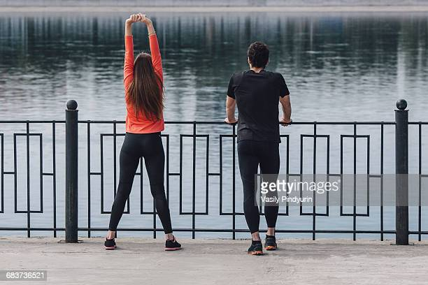 Rear view of people exercising on promenade next to lake