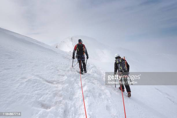 rear view of people hiking on snowcapped mountain against sky - andrea rizzi fotografías e imágenes de stock