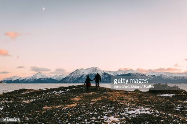 rear view of people holding hands while walking by lake against mountains and sky during sunset - anchorage alaska stock photos and pictures