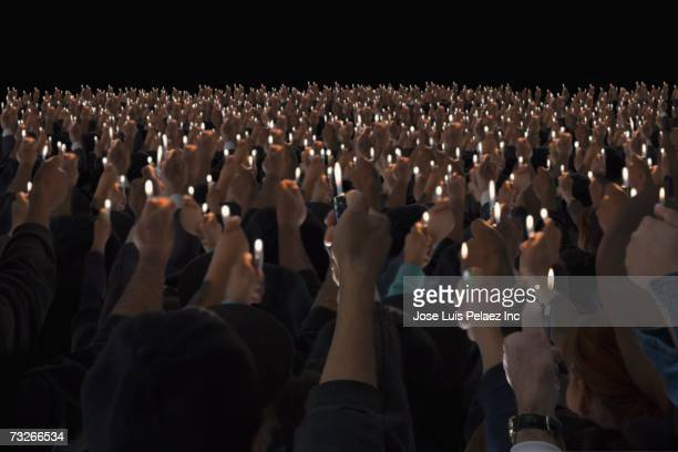 Rear view of people holding lit lighters up in air