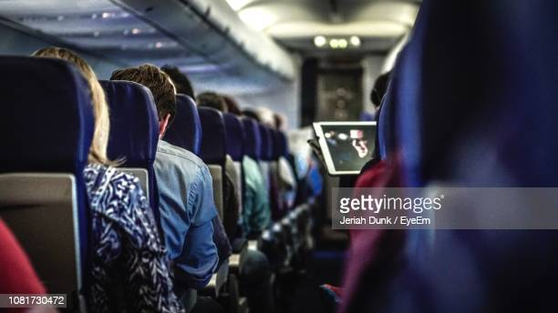rear view of people in airplane - vehicle seat stock pictures, royalty-free photos & images