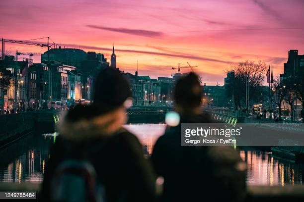 rear view of people in city against sky during sunset - skyline stock pictures, royalty-free photos & images