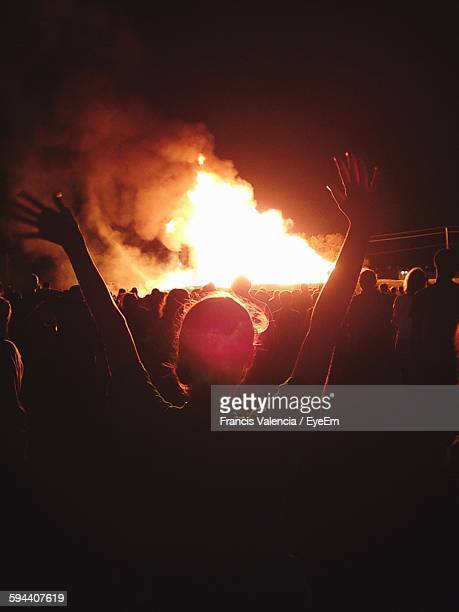 Rear View Of People In Front Of Fire Against Sky At Night