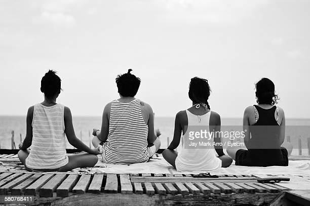 Rear View Of People In Lotus Position Doing Yoga On Beach Against Sky