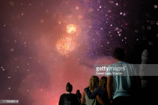 rear view of people looking at fireworks against sky at night - daniel funke stock-fotos und bilder