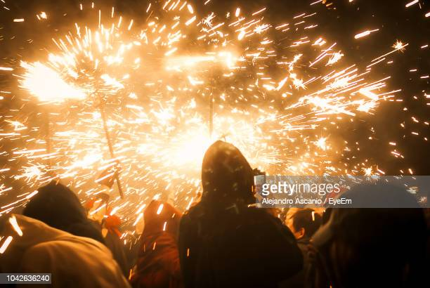 rear view of people looking at fireworks display against sky at night - alejandro ascanio fotografías e imágenes de stock