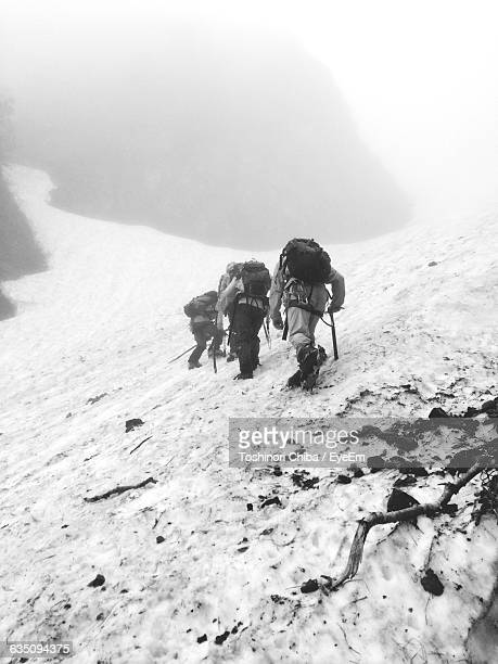 Rear View Of People Mountain Climbing During Winter