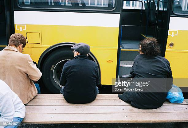 Rear View Of People On Bench Against Bus