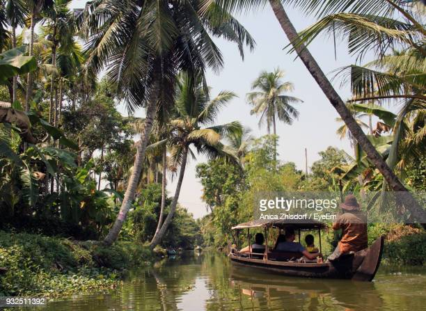 Rear View Of People On Boat Sailing In River Amidst Trees
