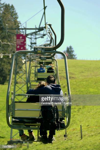 Rear View Of People On Chair Lift Against Sky