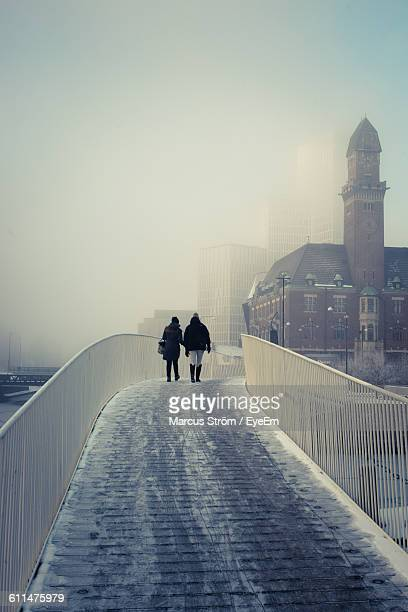 rear view of people on footbridge against sky in city during winter - malmo stock pictures, royalty-free photos & images