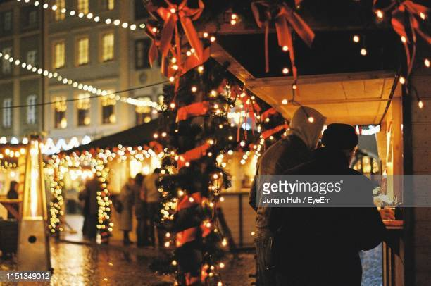 rear view of people on illuminated street at night - warsaw stock pictures, royalty-free photos & images