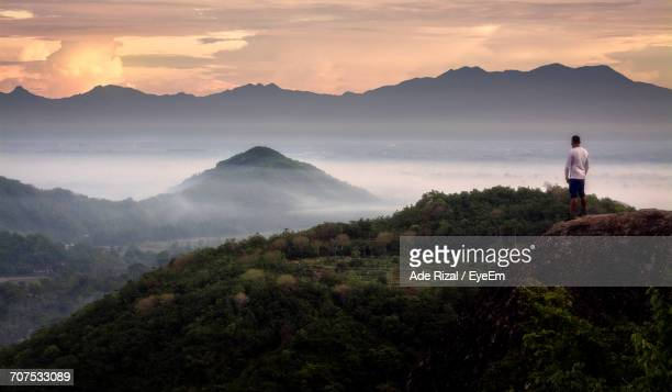 rear view of people on mountain against cloudy sky - ade rizal stock photos and pictures