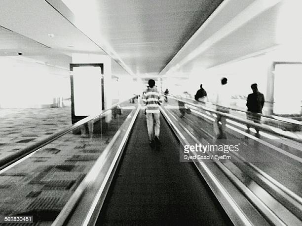 Rear View Of People On Moving Walkway At Airport