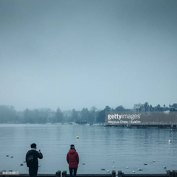 Rear View Of People On Pier By Lake In Foggy Weather