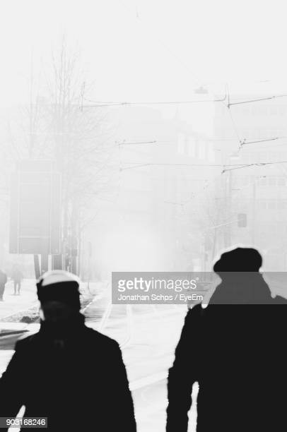Rear View Of People On Road During Foggy Weather