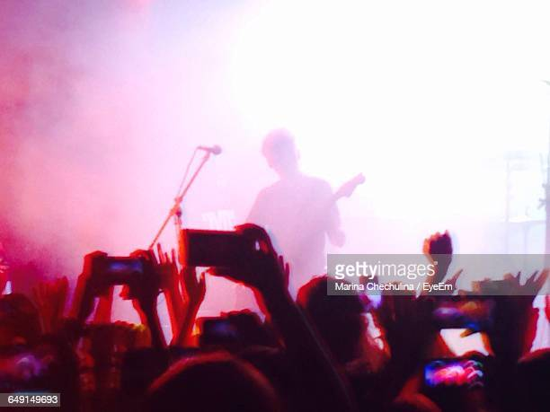 Rear View Of People Photographing Guitarist Performing On Stage