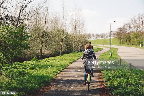Rear View Of People Riding Bicycle On Road During Sunny Day